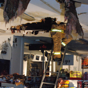 The legs of North Granville fire chief Scott McCullen protrude from a hole in the ceiling below the sport where a Black Friday fire started in Schoony's North Granville Grocery. Nov. 26, 2010.