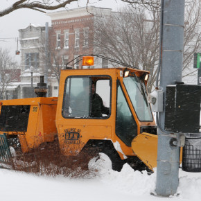 Village worker Nate Baker uses the sidewalk plow on Main Street as the flags on the lawn of TD Bank blow in wind Monday morning. The only major snowstorm of 2010 wound down Dec. 27 after dropping an extimated 12 inches of snow in Granville. Dec. 27, 2010.