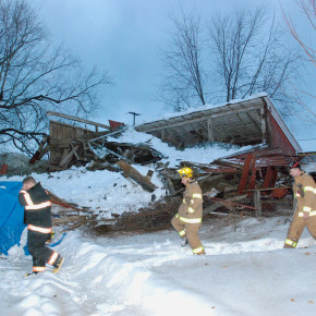 North Granville and Penrhyn fire chiefs Scott McCullen and Milt Dunbar, far right, make thier way around the remains of the County Route 23 barn of Dan Wilson and Susan Knapp. The barn caved in just before 5 p.m. Sunday, no one was injured.