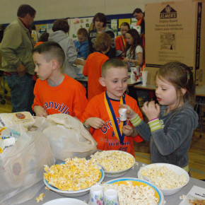 First grader Katie McEachron from Mrs. Gadway's class enjoys her popcorn experiment along with brothers Jack and Connor Farrell.