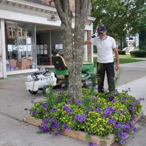 Ernie Wood waters planters on Main Street with the help of the watering cart purchased by Charlie King.
