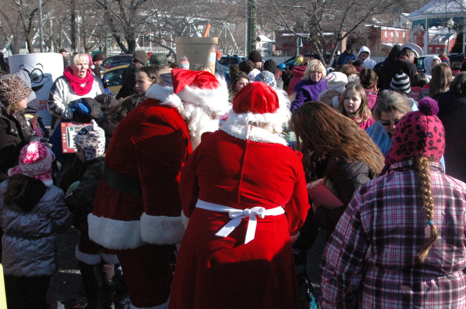Santa Claus and Mrs. Claud give out gifts to kids