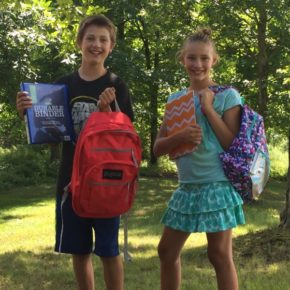 Skyler (left) and Melody Schinski, Ann Schinski's grandchildren, show off some of the gear that will be given away at Saturday's backpack drive.