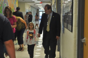 Superintendent Mark Bessen walks a Mary J. Tanner  student to class on the first day of school.