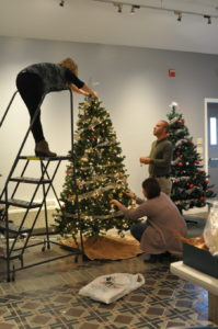 Telescope Casual Furniture employees Kait Rathbun, Michael Zinn and Heather Pauquette decorate their company's tree, which will be auctioned off at the Festival of Trees event at the Slate Valley Museum this Friday.