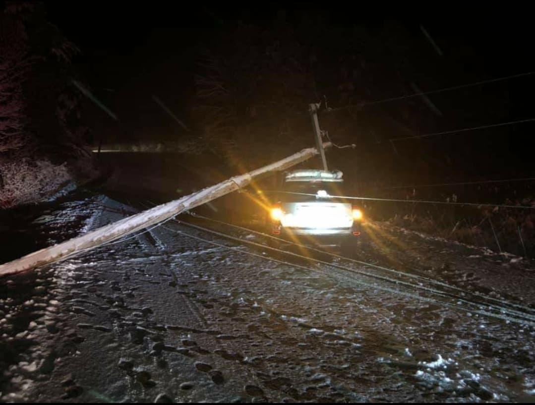 Car hits fallen electric pole